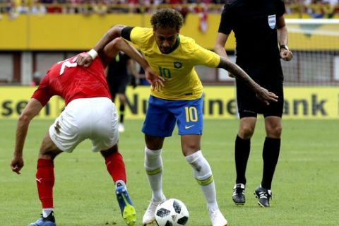 Brazil's Neymar, center, duels for the ball with Austria's Alessandro Schopf during a friendly soccer match between Austria and Brazil at the Ernst Happel Stadium in Vienna, Austria, Sunday, June 10, 2018. (AP Photo/Ronald Zak)