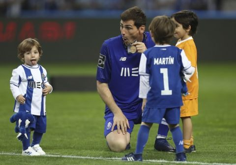 Porto goalkeeper Iker Casillas holds his medal celebrating with children on the pitch at the end of the Portuguese league soccer match between FC Porto and Feirense at the Dragao stadium in Porto, Portugal, Sunday, May 6, 2018. Porto clinched the league title Saturday night, two rounds before the end, when Benfica and Sporting CP tied 0-0 in their Lisbon derby. (AP Photo/Luis Vieira)