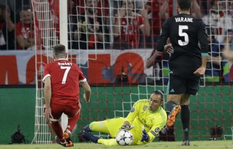 Real Madrid's goalkeeper Keylor Navas saves a ball by Bayern's Franck Ribery, left, as Real Madrid's Raphael Varane, right, looks on during the semifinal first leg soccer match between FC Bayern Munich and Real Madrid at the Allianz Arena stadium in Munich, Germany, Wednesday, April 25, 2018. (AP Photo/Matthias Schrader)