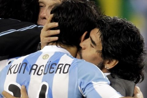 Argentina head coach Diego Maradona, right, kisses Sergio Aguero after the World Cup quarterfinal soccer match between Argentina and Germany at the Green Point stadium in Cape Town, South Africa, Saturday, July 3, 2010.  Germany won 4-0. (AP Photo/Gero Breloer)