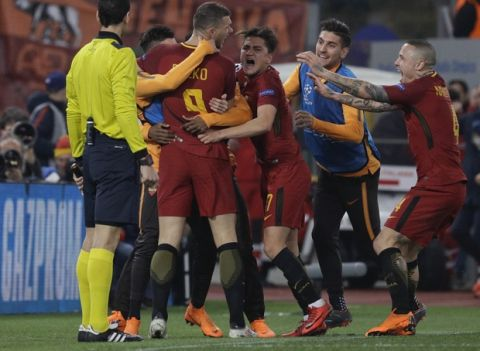 Roma's Edin Dzeko, 3rd from left, celebrates with teammates after scoring his side's opening goalduring a Champions League round of 16 second-leg soccer match between Roma and Shakhtar Donetsk, at the Rome Olympic stadium, Tuesday, March 13, 2018. (AP Photo/Gregorio Borgia)