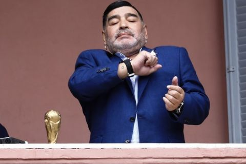 Ο Ντιέγκο Μαραντόνα ποζάρει έχοντας δίπλα του μία ρέπλικα του τροπαίου του Μουντιάλ