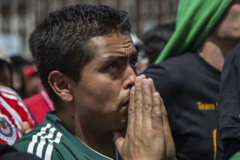 A Mexico fan watches the Mexico vs. Germany World Cup soccer match on an outdoor screen in Mexico City's Zocalo, Sunday, June 17, 2018. Mexico won it's first match against Germany 1-0. (AP Photo/Anthony Vazquez)