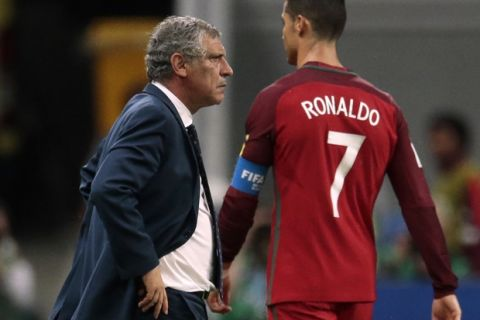 Portugal's Cristiano Ronaldo walks by Portugal coach Fernando Santos during the Confederations Cup, semifinal soccer match between Portugal and Chile, at the Kazan Arena, Russia, Wednesday, June 28, 2017. (AP Photo/Ivan Sekretarev)