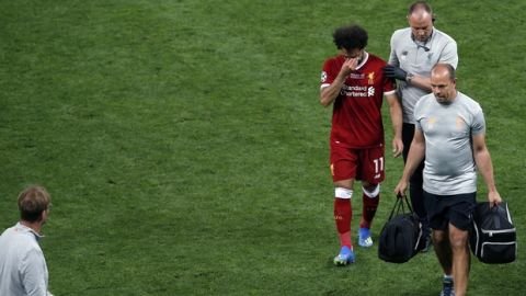 Liverpool's Mohamed Salah leaves the pitch after a collision with Real Madrid's Sergio Ramos during the Champions League Final soccer match between Real Madrid and Liverpool at the Olimpiyskiy Stadium in Kiev, Ukraine, Saturday, May 26, 2018. (AP Photo/Darko Vojinovic)