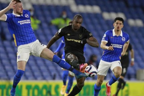 West Ham's Michail Antonio, centre, is tackled by Brighton's Adam Webster during an English Premier League soccer match between Brighton & Hove Albion and West Ham United at the Amex stadium in Brighton, England, Saturday May 15, 2021. (AP Photo/Ian Walton, Pool)