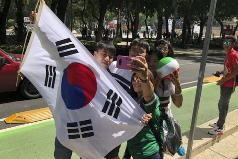 Korean and Mexican fans celebrate after Mexico lost to Sweden in a Russia World Cup soccer match, in Mexico City Wednesday, June 27, 2018. Mexico lost the match but was able to advance to the next round because Korea knocked Germany out of the tournament. (AP Photo/Dario Lopez-Mills)