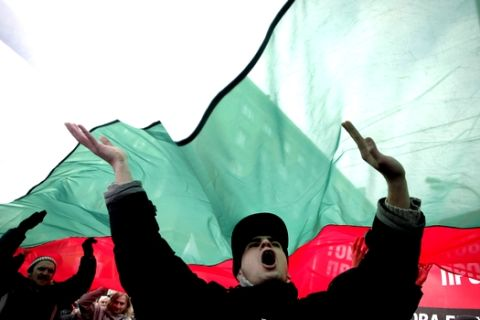"""Bulgarian shouts slogans as they carry giant Bulgarian flag  during a protest against higher electricity and heating bills, in Sofia,  Sunday, Feb. 17, 2013. Thousands of angry Bulgarians chanted """"mafia"""" and """"resignation""""  demanded the expulsion of the three foreign-controlled power distributors that control the local market: Czech Republic's CEZ and Energo-Pro, and Austria's EVN   (AP Photo/Valentina Petrova)"""