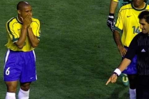 Esfandiar Baharmast, referee from the USA, points at the foul spot  that led to a penalty shot for Norway as Brazil's Roberto Carlos covers his face during the Brazil vs. Norway, Group A, World Cup 98, soccer match at the Velodrome stadium in Marseille, Tuesday, June 23, 1998. The other teams in Group A are Scotland and Morocco.  Norway won 2-1.(AP Photo/Diether Endlicher)
