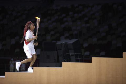 Η Ναόμι Οσάκα ανάβει τη φλόγα στο βωμό του σταδίου στην τελετή έναρξης των Ολυμπιακών Αγώνων