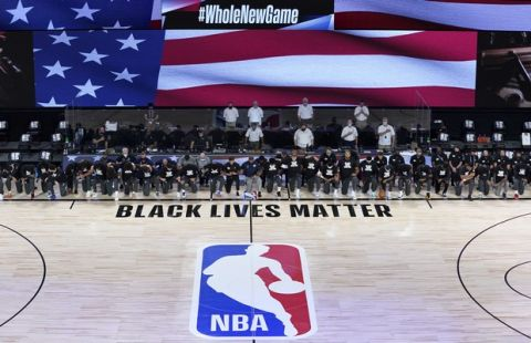 Members of the New Orleans Pelicans and Utah Jazz kneel together around the Black Lives Matter logo on the court during the national anthem before the start of an NBA basketball game Thursday, July 30, 2020, in Lake Buena Vista, Fla. (AP Photo/Ashley Landis, Pool)