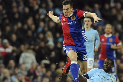 Basel's Kevin Bua, top, challenges for the ball with Manchester City's Yaya Toure during the Champions League, round of 16, second leg soccer match between Manchester City and Basel at the Etihad Stadium in Manchester, England, Wednesday, March 7, 2018. (AP Photo/Rui Vieira)
