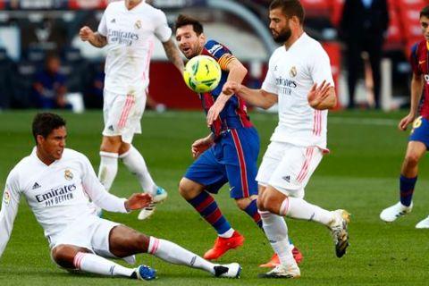 """Ο Λιονέλ Μέσι της Μπαρτσελόνα μονομαχεί με τον Ραφαέλ Βαράν (κάτω) και τον Νάτσο (δεξιά) της Ρεάλ για τη La Liga 2020-2021 στο """"Καμπ Νόου"""", Βαρκελώνη   Σάββατο 24 Οκτωβρίου 2020"""