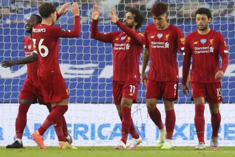 Liverpool's Mohamed Salah, centre, is congratulated by teammates after scoring his team's first goal during the English Premier League soccer match between Brighton and Liverpool at Falmer Stadium in Brighton, England, Wednesday, July 8, 2020. (AP Photo/Catherine Ivill,Pool)