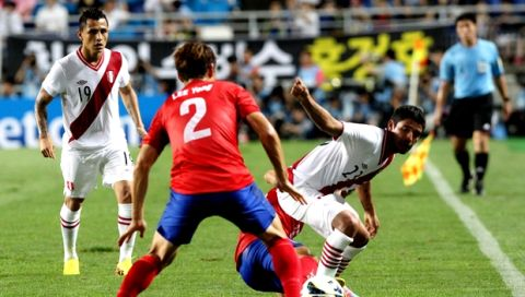 Peru's Reimond Manco, right, fights for the ball against South Korea's Lee Yong, center, during their friendly match in Suwon, South Korea, Wednesday, Aug. 14, 2013. The game ended 0-0. (AP Photo/Ahn Young-joon)