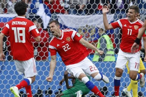 Russia's Artyom Dzyuba, center, celebrates after scoring his side's third goal during the group A match between Russia and Saudi Arabia which opens the 2018 soccer World Cup at the Luzhniki stadium in Moscow, Russia, Thursday, June 14, 2018. (AP Photo/Hassan Ammar)