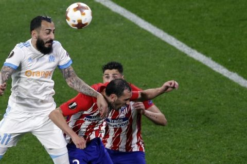 Marseille's Konstantinos Mitroglou, left, heads the ball during the Europa League Final soccer match between Marseille and Atletico Madrid at the Stade de Lyon outside Lyon, France, Wednesday, May 16, 2018. (AP Photo/Christophe Ena)