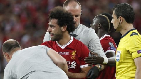 Liverpool's Mohamed Salah is helped my medical staff after injuring himself during the Champions League Final soccer match between Real Madrid and Liverpool at the Olimpiyskiy Stadium in Kiev, Ukraine, Saturday, May 26, 2018. (AP Photo/Pavel Golovkin)