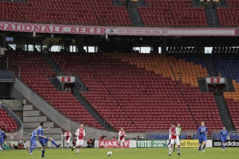 Empty stands are seen in the background as Ajax plays AZ Alkmaar, in blue, during the replay of the soccer match without regular soccer fans at ArenA stadium in Amsterdam, Netherlands, Thursday, Jan. 19, 2012. The Dutch FA ruled that the match be replayed after a fan attacked AZ goalkeeper Esteban Alvarado in the Wednesday Dec. 21, 2011 match. At first the match was to be replayed without fans, but the FA honored Ajax's request to admit 22,000 school children and their teachers to the match. AZ won the match with a 3-2 score. (AP Photo/Peter Dejong)