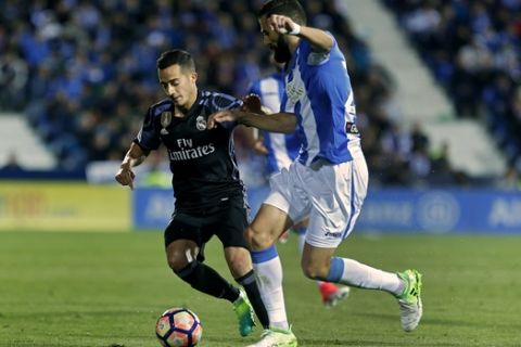 Real Madrid's Lucas Vazquez, left, vies for the ball with Leganes' Dimitrios Siovas during a Spanish La Liga soccer match between Leganes and Real Madrid at the Butarque stadium in Madrid, Wednesday, April 5, 2017. (AP Photo/Francisco Seco)