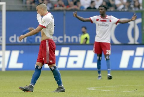Hamburg's Bobby Wood, left, leaves the pitch after he received a red card during the German Bundesliga soccer match between Hamburger SV and VfL Borussia Moenchengladbach in Hamburg, Germany, Saturday, May 12, 2018. (AP Photo/Michael Sohn)