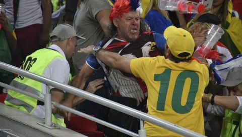 Serbia and Brazilia soccer fans fight each other during the group E match between Serbia and Brazil, at the 2018 soccer World Cup in the Spartak Stadium in Moscow, Wednesday, June 27, 2018. (AP Photo)