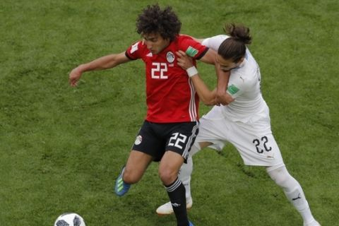 Egypt's Amr Warda, left, vie for the ball with Uruguay's Martin Caceres, right, during the group A match between Egypt and Uruguay at the 2018 soccer World Cup in the Yekaterinburg Arena in Yekaterinburg, Russia, Friday, June 15, 2018. (AP Photo/Vadim Ghirda)