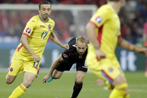 Albania's Migjen Basha, center, looks the ball as Romania's Lucian Sanmartean, left, goes for the ball during the Euro 2016 Group A soccer match between Romania and Albania at the Grand Stade in Decines-Charpieu, near Lyon, France, Sunday, June 19, 2016. (AP Photo/Pavel Golovkin)