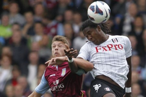 Fulham's Hugo Rodallega, right, competes with Aston Villa's Nathan Baker during their English Premier League soccer match at Craven Cottage, London, Saturday, Oct. 20, 2012. (AP Photo/Sang Tan)