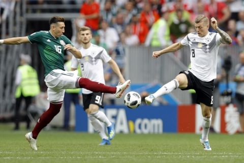 Mexico's Hector Herrera, left, vies for the ball with Germany's Toni Kroos during the group F match between Germany and Mexico at the 2018 soccer World Cup in the Luzhniki Stadium in Moscow, Russia, Sunday, June 17, 2018. (AP Photo/Victor R. Caivano)
