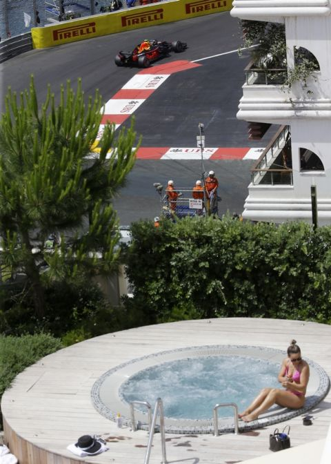 The Netherlands driver Max Verstappen, top, steers his Red Bull as woman sunbathes during the third free practice at the Monaco racetrack, in Monaco, Saturday, May 26, 2018. The Formula one race will be held on Sunday. (AP Photo/Luca Bruno)