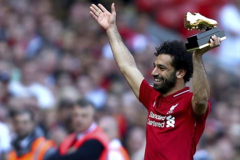 Liverpool's Mohamed Salah lifts up his golden boot award after the English Premier League soccer match against Brighton & Hove Albion at Anfield, Liverpool, England, Sunday, May 13, 2018. (Dave Thompson/PA via AP)