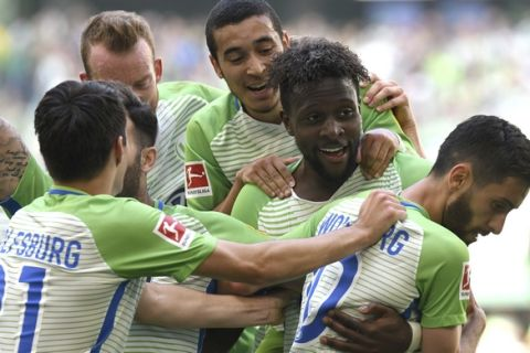 Wolfsburg's Divock Origi, second from right, celebrates after scoring his side's second goal in the German Bundesliga soccer match between VfB Wolfsburg and FC Cologne in Wolfsburg, northern Germany, Saturday, May 12, 2018. (Peter Steffen/dpa via AP)