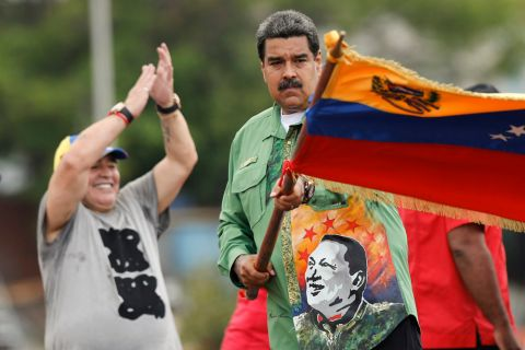 Venezuela's President Nicolas Maduro waves his country's flag as Argentina's former soccer star Diego Maradona applauds during a closing campaign rally in Caracas, Venezuela, Thursday, May 17, 2018. Maduro is seeking a new six-year mandate, and despite crippling hyperinflation and widespread shortages of food and medicine, he is widely expected to win the May 20 election that opponents have denounced as a fraud and have been condemned by much of the international community. (AP Photo/Ariana Cubillos)