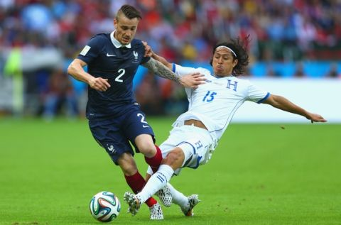 PORTO ALEGRE, BRAZIL - JUNE 15: Mathieu Debuchy of France holds off a challenge by Roger Espinoza of Honduras during the 2014 FIFA World Cup Brazil Group E match between France and Honduras at Estadio Beira-Rio on June 15, 2014 in Porto Alegre, Brazil.  (Photo by Jeff Gross/Getty Images)