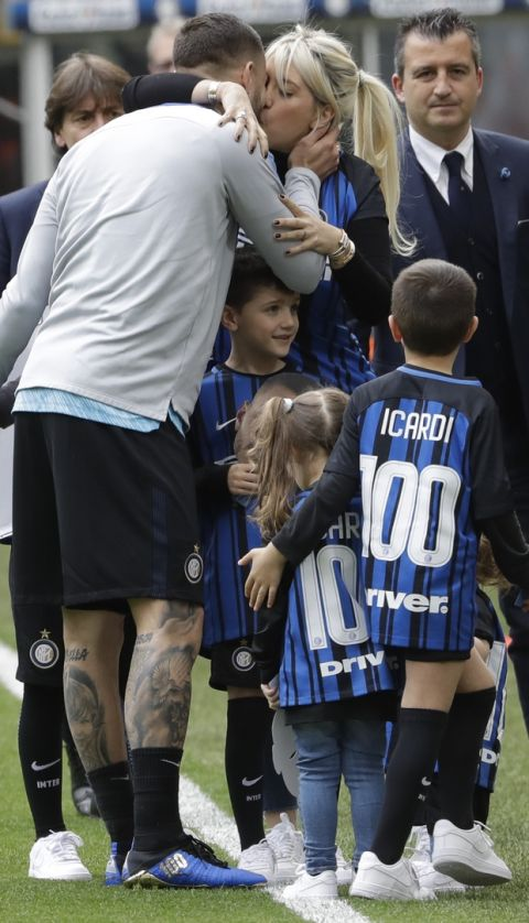 Inter Milan's Mauro Icardi kisses his wife Wanda Nara after receiving a prize for his 100 goal with the Inter Milan jersey, prior to the start of a Serie A soccer match between Inter Milan and Hellas Verona, at the San Siro stadium in Milan, Italy, Saturday, March 31, 2018. (AP Photo/Luca Bruno)