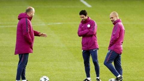 Manchester City manager Pep Guardiola, right, and coach Mikel Arteta, centre, during a training session at the City Football Academy, Manchester, England, Tuesday, Sept. 12, 2017.  (Martin Rickett/PA via AP)