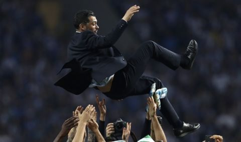 Porto coach Sergio Conceicao is thrown in the air by the players at the end of the Portuguese league soccer match between FC Porto and Feirense at the Dragao stadium in Porto, Portugal, Sunday, May 6, 2018. Porto clinched the league title Saturday night, two rounds before the end, when Benfica and Sporting CP tied 0-0 in their Lisbon derby. (AP Photo/Luis Vieira)