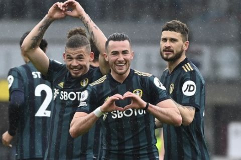 Leeds United's Jack Harrison, center, celebrates after scoring his side's second goal during the English Premier League soccer match between Burnley and Leeds United at Turf Moor in Burnley, England, Saturday May 15, 2021. (Gareth Copley/Pool via AP)