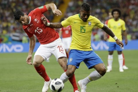 Switzerland's Blerim Dzemaili, left, and Brazil's Paulinho struggle for the ball during the group E match between Brazil and Switzerland at the 2018 soccer World Cup in the Rostov Arena in Rostov-on-Don, Russia, Sunday, June 17, 2018. (AP Photo/Andre Penner)
