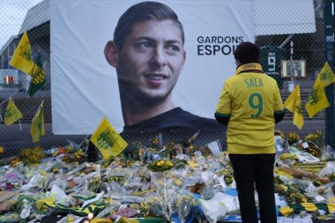"""FILE - In this Wednesday, Jan. 30, 2019, file photo, a Nantes soccer team supporters stops by a poster of Argentinian player Emiliano Sala and reading """"Let's keep hope"""" outside La Beaujoire stadium before the French soccer League One match Nantes against Saint-Etienne, in Nantes, western France. On Sunday, Feb. 3, 2019, the man leading a private search for the missing plane carrying Argentine soccer player Emiliano Sala says the wreckage has been found. (AP Photo/Thibault Camus, File)"""