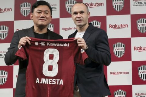Former Barcelona player Andres Iniesta, right, holds his new uniform with Hiroshi Mikitani, left, owner of Vissel Kobe, during a press conference announcing Iniesta move to Japan's Vissel Kobe in Tokyo Thursday, May 24, 2018. (AP Photo/Eugene Hoshiko)