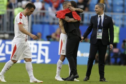 Serbia's Aleksandar Kolarov, second left, is greeted by his coach Mladen Krstajic at the end of the group E match between Costa Rica and Serbia at the 2018 soccer World Cup in the Samara Arena in Samara, Russia, Sunday, June 17, 2018. Kolarov scored once in Serbia's 1-0 victory. (AP Photo/Natacha Pisarenko)