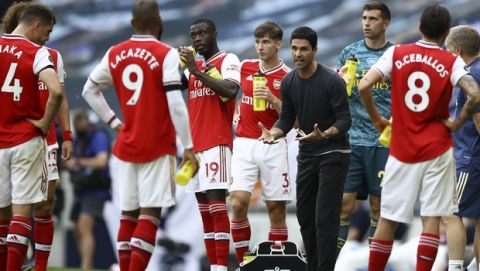 Arsenal's head coach Mikel Arteta, center right, talks to the players during the English Premier League soccer match between Tottenham Hotspur and Arsenal at the Tottenham Hotspur Stadium in London, England, Sunday, July 12, 2020. (Tim Goode/Pool via AP)