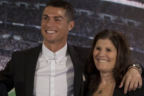 Real Madrid's Cristiano Ronaldo, center, poses his mother Maria Dolores dos Santos Aveiro, right and with the club's President Florentino Perez after signing a new contract at the Santiago Bernabeu stadium in Madrid, Spain, Monday, Nov. 7, 2016. Real Madrid have extend Ronaldo's contract until June 2021, when the three-time world player of the year will be 36. Financial details were not released, although the star forward is expected to remain the team's top-paid player. (AP Photo/Paul White)