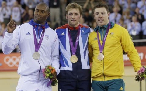 Britain's Jason Kenny shows the gold medal of the track cycling men's sprint event, flanked by Silver Medalist Gregory Bauge, of France, left, and Bronze medalist Shane Perkins, of Australia, at the 2012 Summer Olympics, Monday, Aug. 6, 2012, in London. (AP Photo/Sergey Ponomarev)