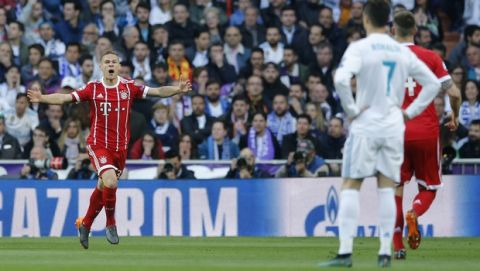 Real Madrid's Cristiano Ronaldo, second right, looks on as Bayern's Joshua Kimmich celebrates after scoring the opening goal during the Champions League semifinal second leg soccer match between Real Madrid and FC Bayern Munich at the Santiago Bernabeu stadium in Madrid, Spain, Tuesday, May 1, 2018. (AP Photo/Paul White)
