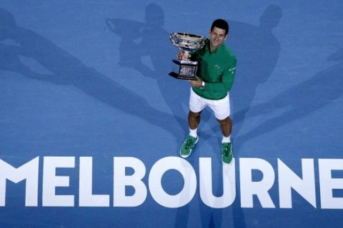 Serbia's Novak Djokovic holds the Norman Brookes Challenge Cup after defeating Austria's Dominic Thiem in the men's singles final of the Australian Open tennis championship in Melbourne, Australia, early Monday, Feb. 3, 2020. (AP Photo/Andy Wong)