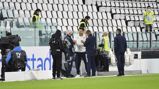 Juventus goalie Gianluigi Buffon, centre, stands on the pitch of the Allianz Stadium in Turin, Italy, Sunday, Oct. 4, 2020 ahead of the scheduled Serie A soccer match between Juventus and Napoli. Napoli is likely to be handed a 3-0 loss by the Italian leagues judge for failing to show for its Serie A match at Juventus on Sunday night. Napoli did not travel to Turin for the match after local health authorities ordered the squad into quarantine after two players tested positive for the coronavirus. (Tano Pecoraro/LaPresse via AP)