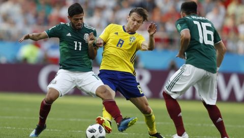 Mexico's Carlos Vela, left, and Sweden's Albin Ekdal, center, challenge for the ball during the group F match between Mexico and Sweden, at the 2018 soccer World Cup in the Yekaterinburg Arena in Yekaterinburg, Russia, Wednesday, June 27, 2018. (AP Photo/Eduardo Verdugo)